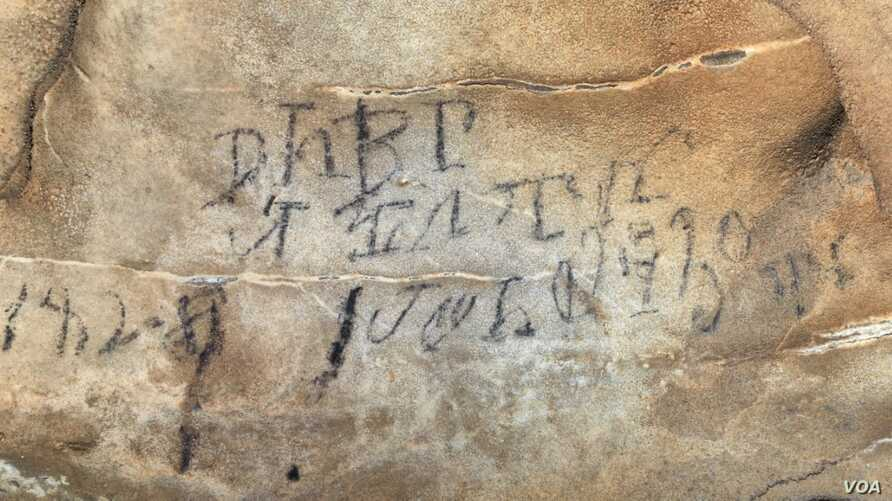An inscription on the Manitou Cave wall, written in the Cherokee syllabary, identifies writers as stickball team leader and is dated April 30, 1828.  Photo courtesy Beau Carroll, archaeologist, Eastern Band of Cherokee.