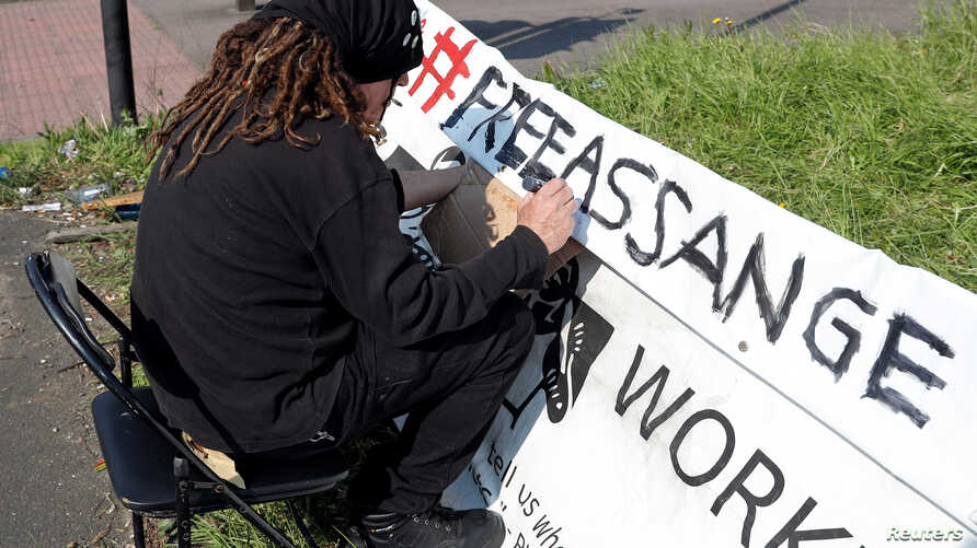 A protester writes his sign outside HMP Belmarsh prison where WikiLeaks founder Julian Assange is held, in London, Britain, April 15, 2019.