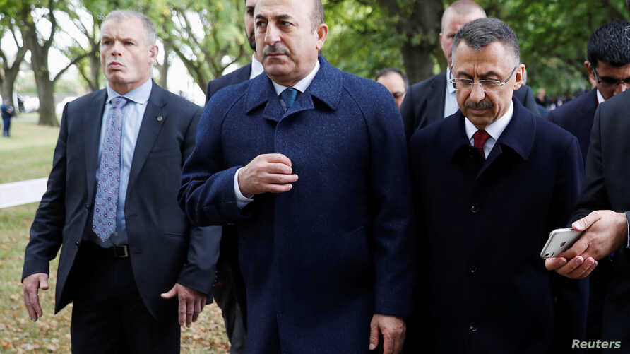 FILE - Turkey's Foreign Minister Mevlut Cavusoglu, center, walks to pay respects to the victims of the mosque shooting, in Christchurch, New Zealand, March 18, 2019.