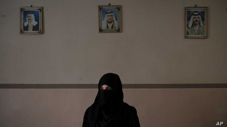 FILE - Khadija Abd poses for a portrait in her family's house in Mosul, Iraq,  Apr.  14, 2019. On a chilly January evening, the Abd family had just finished supper at their farm when the two men with guns burst into the room.