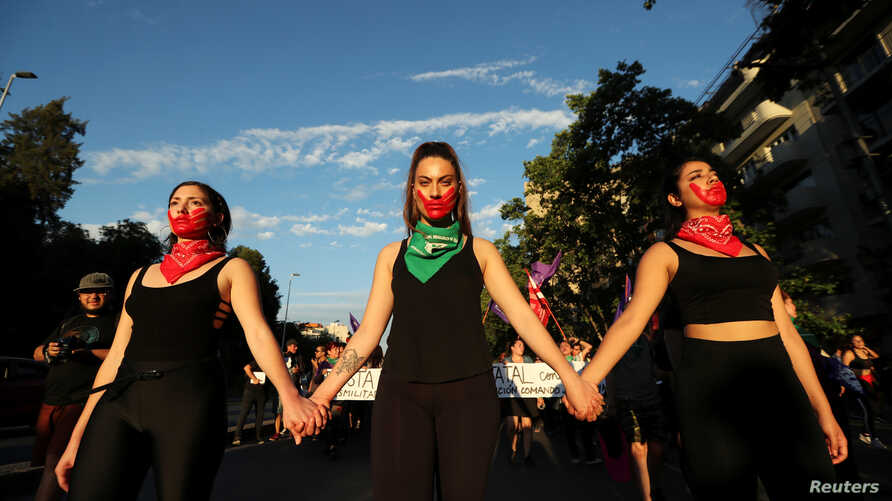 FILE - Demonstrators attend a march demanding an end to sexism and gender violence in Santiago, Chile, Nov. 22, 2018.
