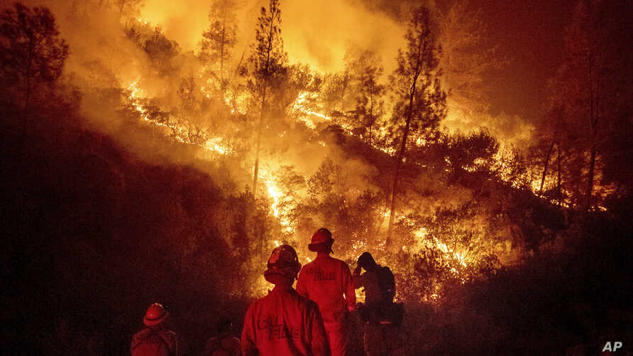 FILE - Firefighters monitor a backfire while battling the Ranch Fire, part of the Mendocino Complex Fire near Ladoga, Calif., Aug. 7, 2018. A nationwide telecommunications company that slowed internet service to firefighters as they battled the largest wi