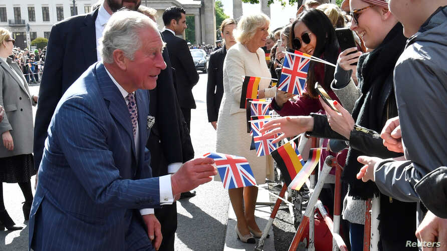 Britain's Prince Charles picks up a Union Jack flag dropped by a well-wisher as he greets the crowd at the Brandenburg Gate in Berlin, May 7, 2019.