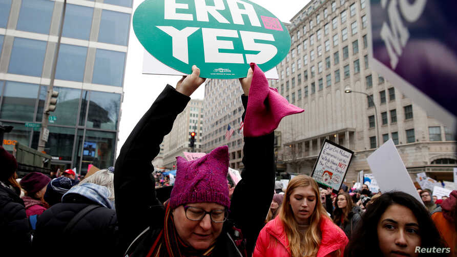 FILE - A demonstrator holds a sign calling for an equal rights amendment (ERA) during in the Third Annual Women's March at Freedom Plaza in Washington, Jan. 19, 2019.