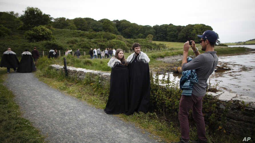 """FILE- In this June 13, 2014, file photo """"Game of Thrones"""" fans stop for a picture on their way to Audleys field and castle,in Northern Ireland."""