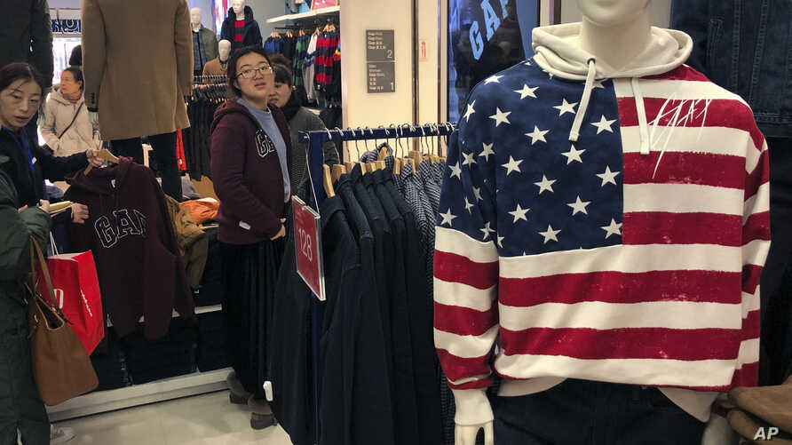 FILE - A woman tries out a sweater at a U.S. retailer GAP's flagship store in Beijing, China.