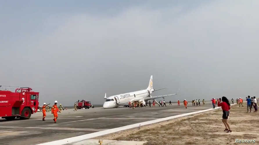 A passenger records the scene on her phone as firefighters attend to the scene after Myanmar National Airlines flight UB103 landed without a front wheel at Mandalay International Airport in Tada-U, Myanmar, May 12, 2019 in this image taken from socia...