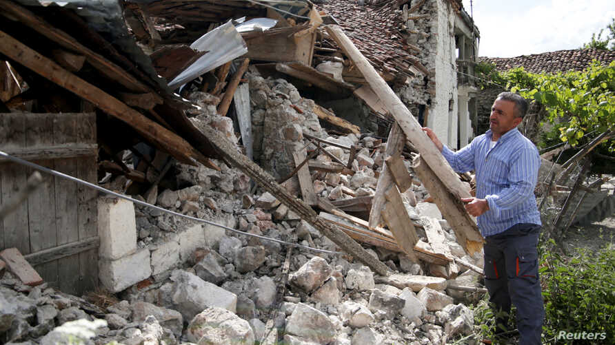 A man clears debris outside a damaged building after an earthquake stroked the area in Floq, Albania, June 1, 2019.