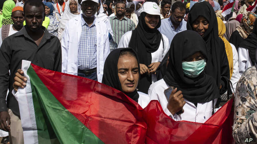 A protester carries a Sudanese flag as they chant against military rule and demand the prosecution of former officials, at the Armed Forces Square, in Khartoum, Sudan, April 28, 2019.