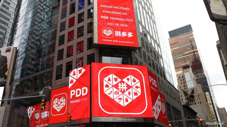 FILE - A display at the Thomson Reuters building shows a message after Chinese online group discounter Pinduoduo Inc. (PDD) was listed on the Nasdaq exchange in Times Square in New York City, New York, July 26, 2018.