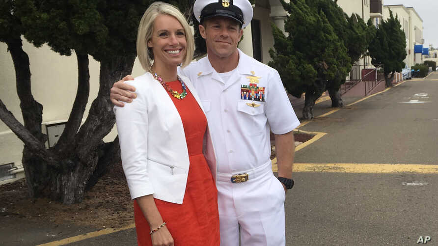 Navy Special Operations Chief Edward Gallagher embraces his wife, Andrea Gallagher, after leaving a military courtroom on Naval Base San Diego, Thursday, May 30, 2019, in San Diego. The decorated Navy SEAL facing a murder trial in the death of an Islamic State prisoner was freed Thursday from custody after a military judge cited interference by prosecutors. (AP Photo/Julie Watson)