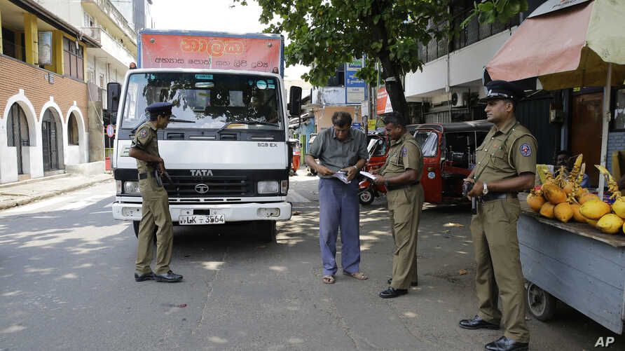 Sri Lankan police officers perform a security check on a truck at a roadside in Colombo, Sri Lanka, April 25, 2019.