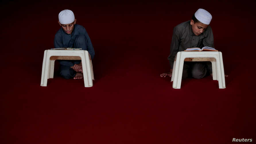 FILE - Students memorize the Quran at the Al-Nadwa Madrassa in Murree, Pakistan.
