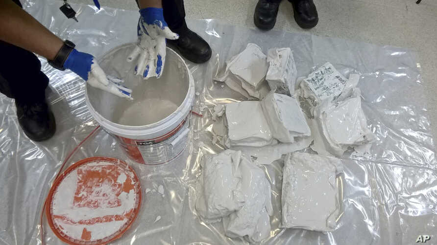 In this undated recent photo provided by the Australian Federal Police, an investigator removes packages of the methamphetamine drug from containers in Sydney.