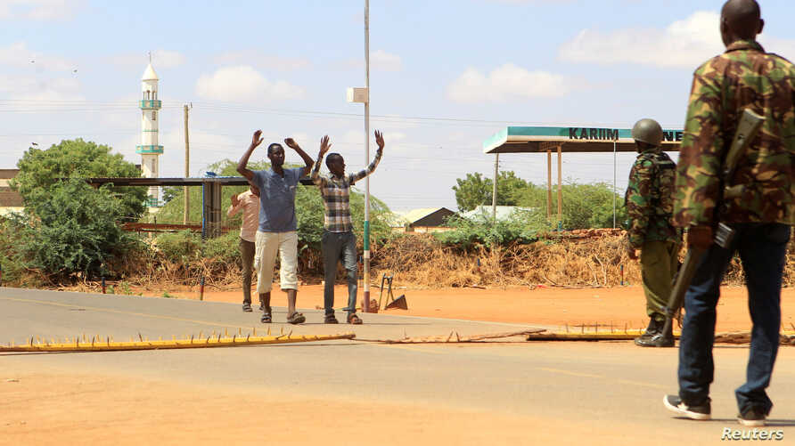 Security officers question civilians at a roadblock near the site where gunmen abducted two Cuban doctors as they were on their way to work, in Mandera county, Kenya, April 12, 2019.