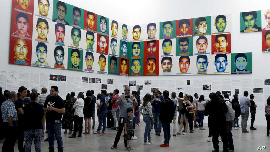 People stand under the portraits of 43 college students who went missing in 2014 in an apparent massacre, by Chinese concept artist and government critic Ai Weiwei at the Contemporary Art University Museum in Mexico City, Mexico, April 13, 2019.