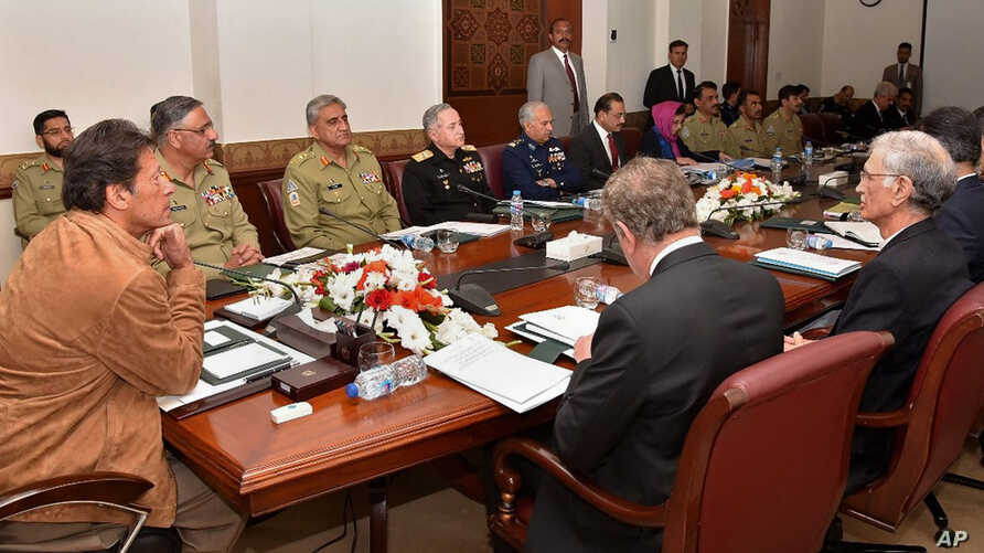 In this photo released by the Press Information Department, Pakistan Prime Minister Imran Khan, left, chairs a meeting of the country's National Security Committee, in Islamabad, Pakistan, Feb. 21, 2019.