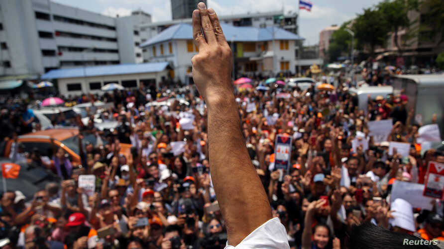 FILE - Thanathorn Juangroongruangkit, leader of the Future Forward Party flashes a three finger salute to his supporters as he leaves a police station after hearing a sedition complaint filed by the army in Bangkok, Thailand, Apr. 6, 2019.