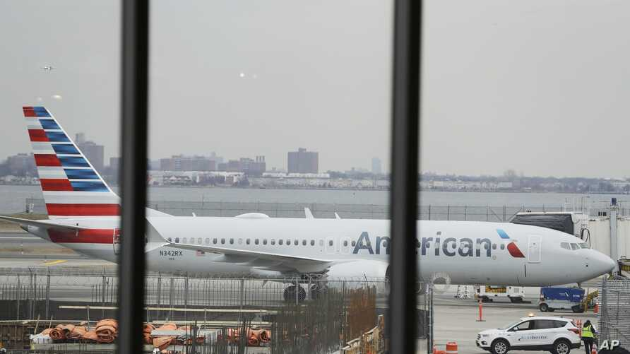 An American Airlines Boeing 737 MAX 8  plane sits at a boarding gate at LaGuardia Airport Wednesday, March 13, 2019, in New York.