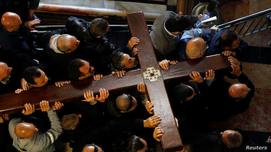Worshippers carry a large wooden cross into the Church of the Holy Sepulchre during Good Friday procession along the Via Dolorosa in Jerusalem's Old City, April 19, 2019.