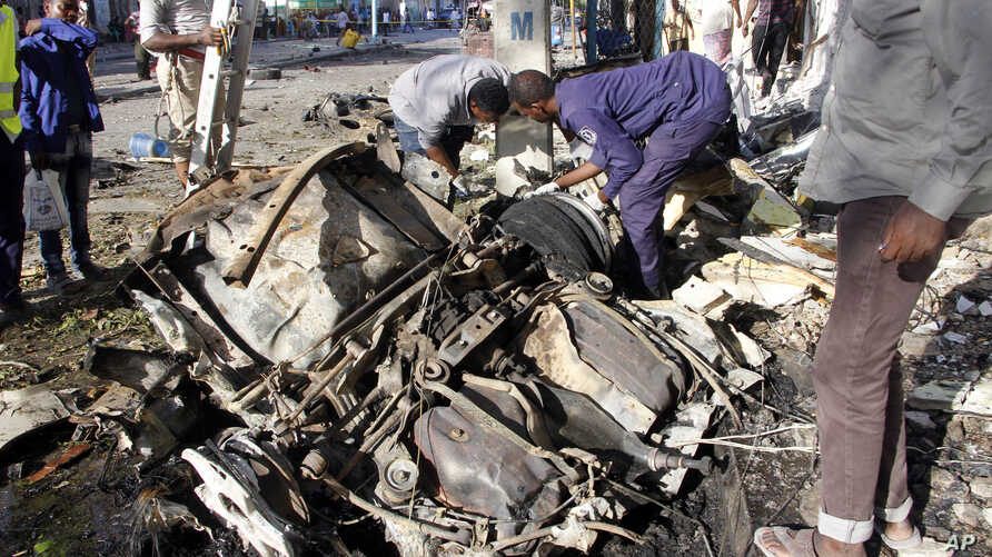 Somalian police examine the wreckage of the car after car bomb exploded in Mogadishu, Somalia, April 17, 2019.