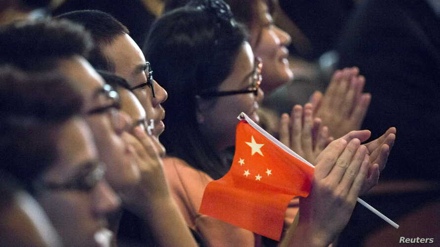 FILE - Students clap while Chinese President Xi Jinping delivers a speech during a visit to Lincoln High School in Tacoma, Washington, Sept. 23, 2015.