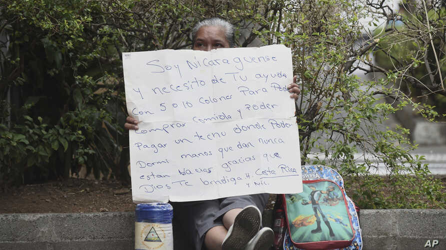 "FILE - A Nicaraguan exile, who wishes to only be identified by her nickname ""La Profe,"" Spanish for ""the teacher,"" holds a sign asking for spare change in Alajuela, Costa Rica, March 29, 2019."