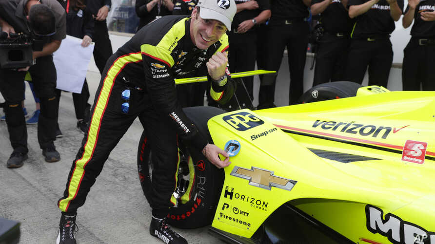 Simon Pagenaud of France places the pole award on his car during following qualifications for the Indianapolis 500 IndyCar auto race at Indianapolis Motor Speedway, in Indianapolis, May 19, 2019.