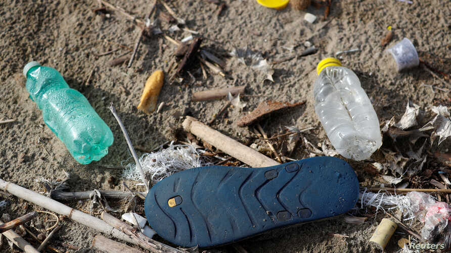 FILE - Plastic bottles and a flip-flop lie on the sand at Maccarese beach in Rome, Italy, Nov. 21, 2018.