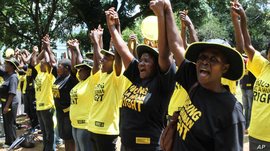 FILE - Residents of various townships across Zimbabwe hold hands during an Amnesty International event in Harare, Zimbabwe, March 23, 2012.