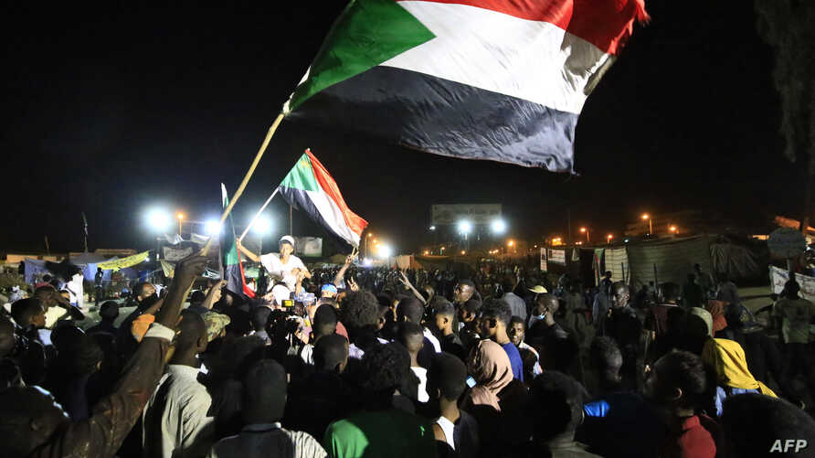 Sudanese protesters celebrate after an agreement was reached with the military council to form a three-year transition period for transferring power to a full civilian administration, in Khartoum, May 15, 2019.