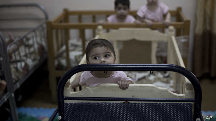 FILE - In this Aug. 15, 2018 file, photo, baby girls stand up in their cribs at Salhiya Orphanage, which now hosts foreign and Iraqi children of Islamic State militants, in Baghdad, Iraq.