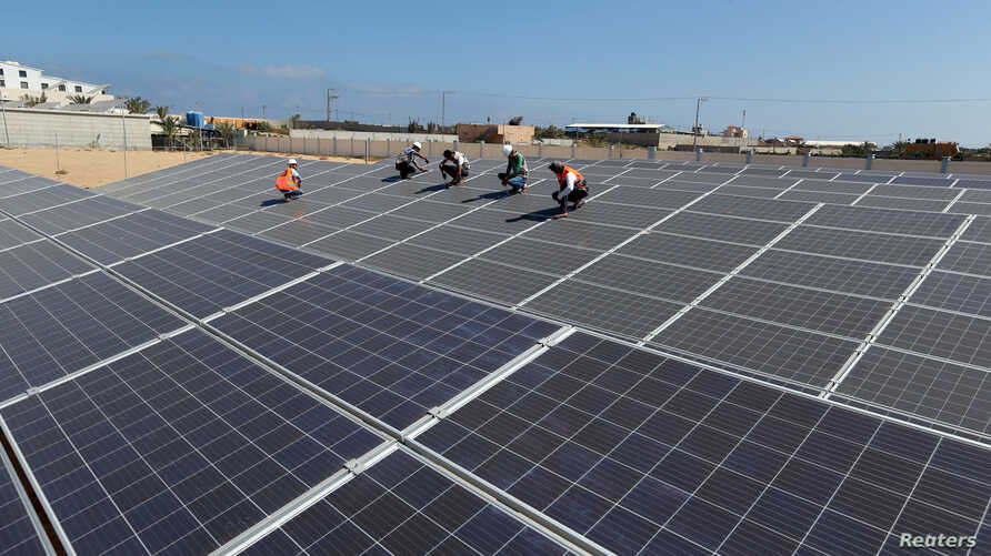 Palestinian workers install solar panels at Khan Younis Waste Water Treatment Plant, in the southern Gaza Strip July 31, 2018. Picture taken July 31, 2018.