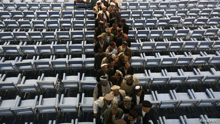 FILE - Participants of a jirga leave an assemply space in Kabul, Afghanistan, Nov. 24, 2013.
