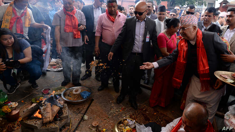 Nepali Prime Minister Khadga Prasad Sharma Oli known as KP Sharma Oli (R) takes part in a ritual as he visits the reconstruction site of Kathmandu Durbar Square, which was damaged by the 2015 earthquake, on the fourth anniversary of the disaster in K...