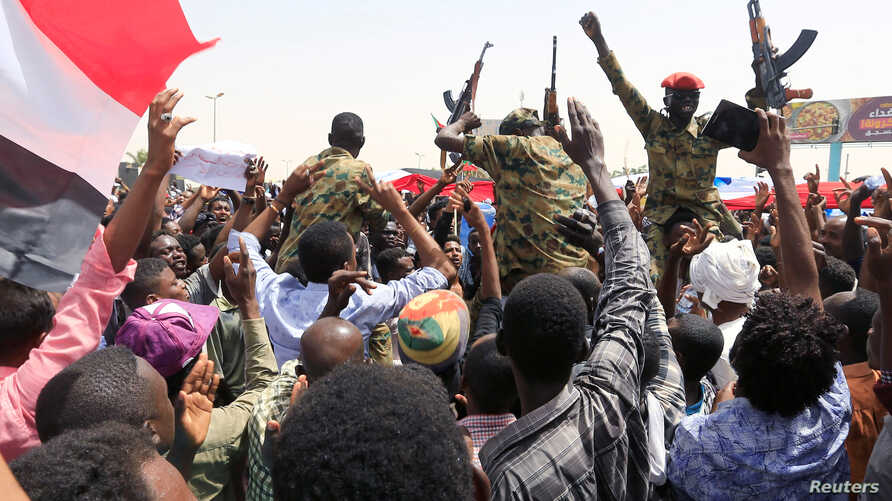 Sudanese military officers and demonstrators ride atop a military tanker as they protest against the army's announcement that President Omar al-Bashir would be replaced by a military-led transitional council, near Defense Ministry in Khartoum, Sudan,...