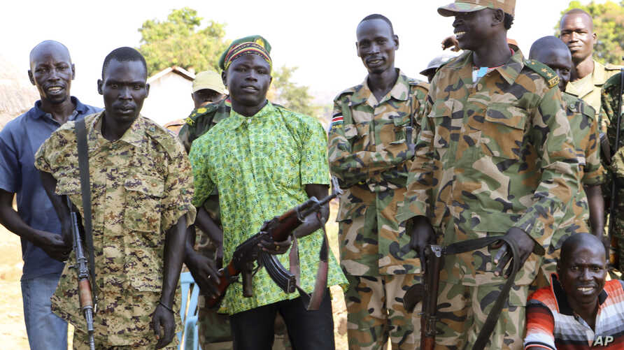 Government and opposition soldiers pose for a picture in the government barracks in Kajo Keji town, where 10 opposition soldiers were staying with the government troops in a makeshift soldier swap, in Kajo Keji county, South Sudan, Jan. 6, 2019.