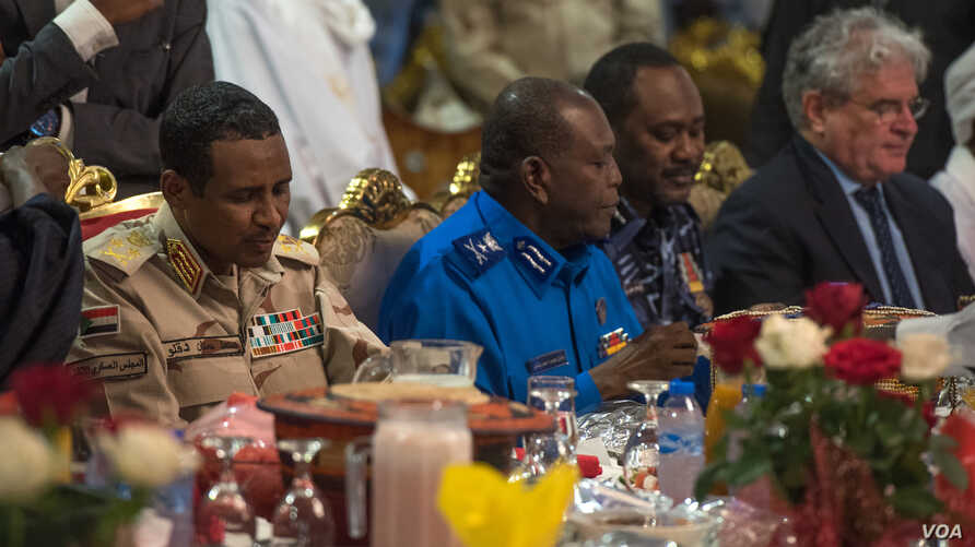 Militia commander Mohamed Hamdan Hemeti Dagolo (left, in khaki uniform) eats an Iftar meal with U.S. Charge D'Affaires Steven Koutsis (far right, in suit), in Khartoum, Sudan, May 18, 2019.