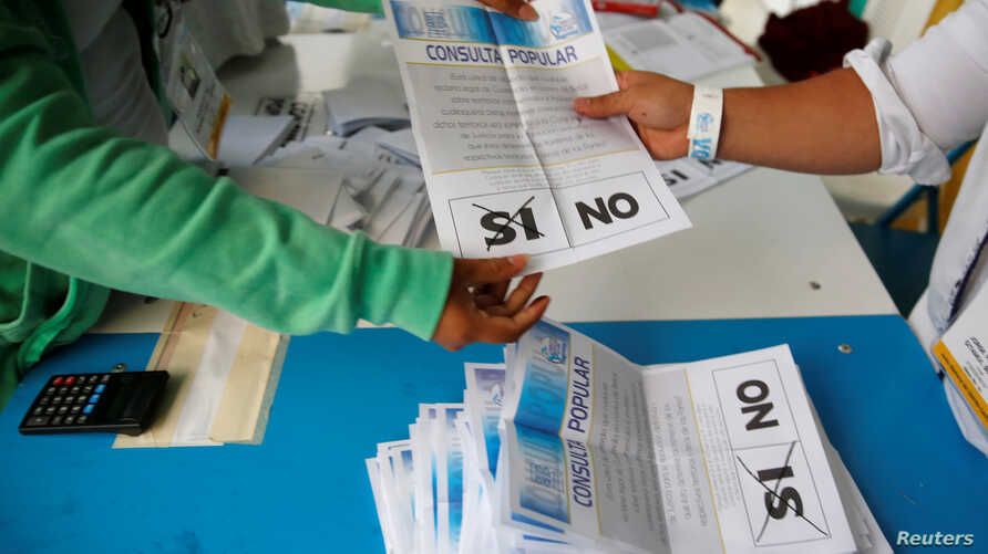 FILE - Workers count ballots after polls closed at a polling station during a referendum on a border dispute with Belize in Guatemala City, Guatemala, April 15, 2018.