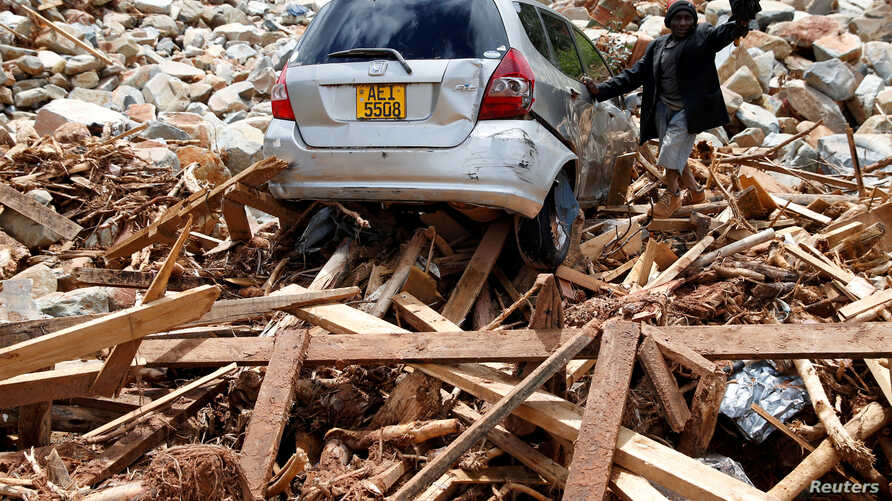 FILE - A man gestures next to his car after it was swept into debris left by Cyclone Idai in Chimanimani, Zimbabwe, March 23, 2019.