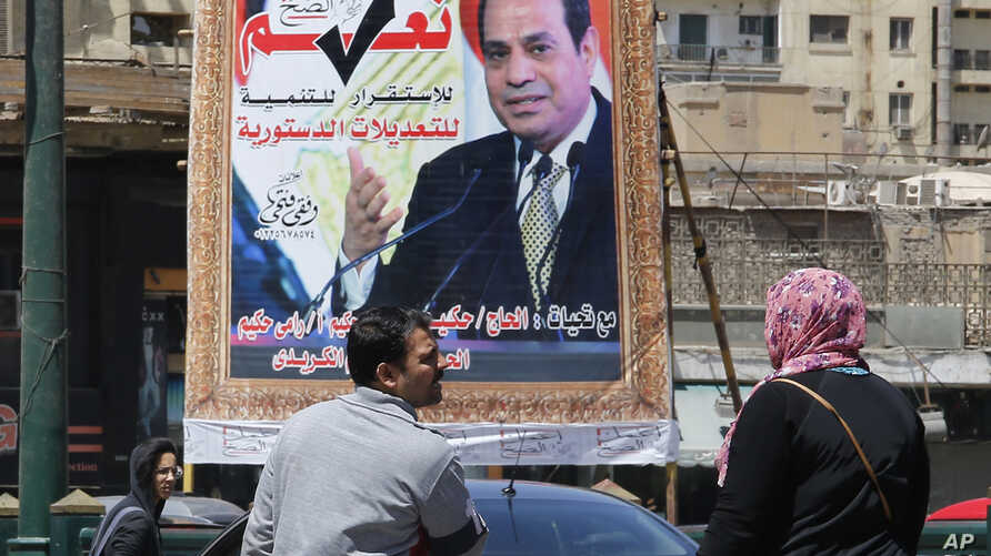 People walk past a banner supporting proposed amendments to the Egyptian constitution with a poster of Egyptian President Abdel-Fattah el-Sissi in Cairo, Egypt, April 16, 2019.