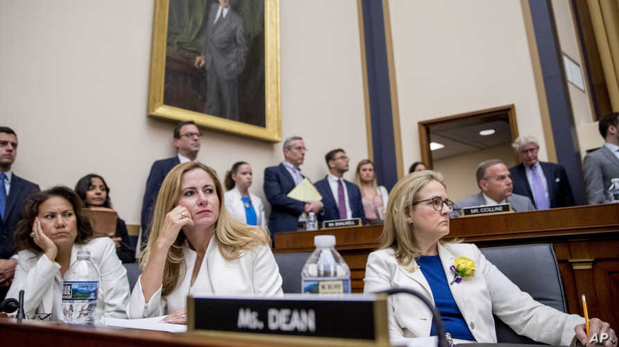 From left, Rep. Veronica Escobar, D-Texas, Rep. Debbie Mucarsel-Powell, D-Fla., and Rep. Madeleine Dean, D-Pa., wear white and yellow roses to commemorate the 19th Amendment on Capitol Hill in Washington, Tuesday, May 21, 2019.