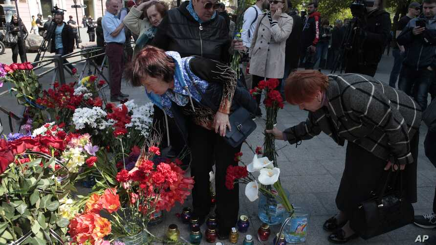 People lay flowers as they gather to commemorate the five-year anniversary of deadly clashes which killed dozens of demonstrators supporting Ukraine's government and pro-Russia protesters, in Odessa, Ukraine, May 2, 2019.