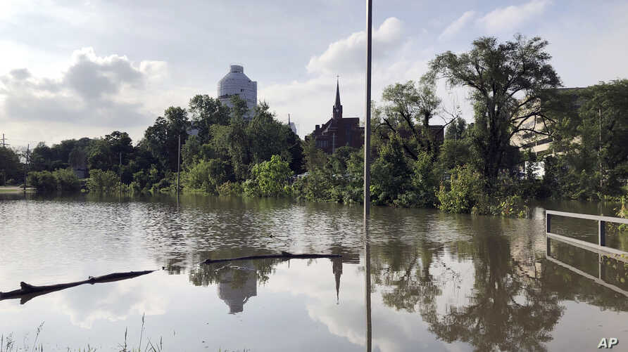The Missouri Capitol, which is wrapped in plastic while under renovation, is reflected in floodwaters that submerged a parking lot for state employees in Jefferson City, Mo., on May 29, 2019.