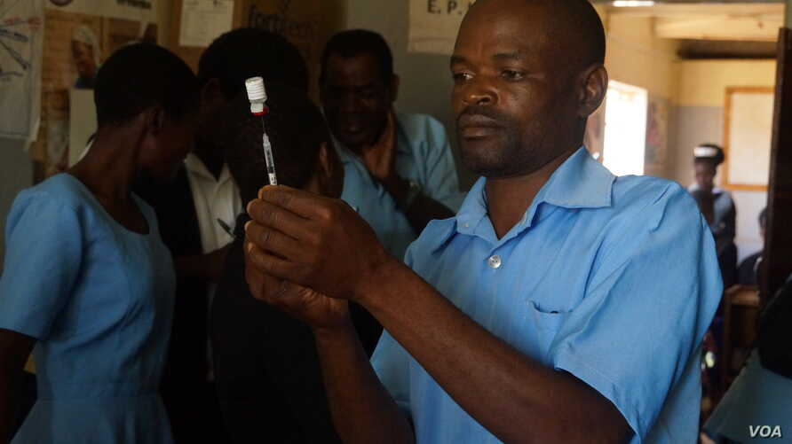 A medical worker at Likuni Community Hospital, in Lilongwe, Malawai draws the malaria vaccine into a syringe for vaccination.