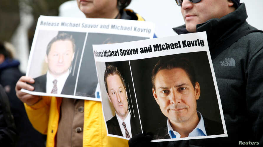 People hold signs calling for China to release Canadian detainees Michael Spavor and Michael Kovrig during an extradition hearing for Huawei Technologies Chief Financial Officer Meng Wanzhou at the B.C. Supreme Court in Vancouver, British Columbia, C...