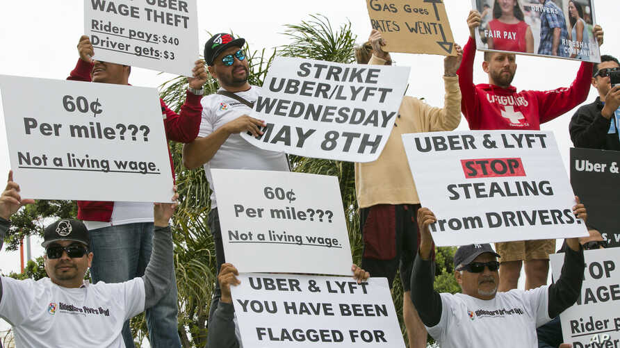Drivers for ride-hailing giants Uber and Lyft rally at a park near Los Angeles International Airport, May, 8, 2019, in Los Angeles. Some drivers for ride-hailing giants Uber and Lyft turned off their apps to protest what they say are declining wages ...