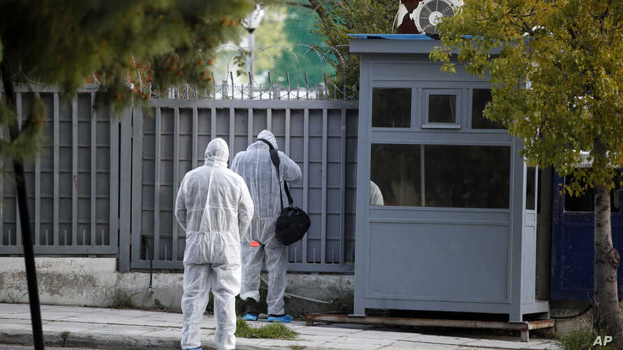 FILE - Forensic experts search the area outside the Russian Consulate in Athens in the wake of an explosion, March 22, 2019. On April 18, 2019, a Greek anarchist group claimed responsibility for exploding a grenade at the site.