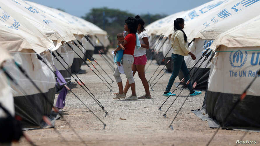 Venezuelan migrant women walk through a camp run by the UN refugee agency UNHCR in Maicao, Colombia, May 7, 2019.