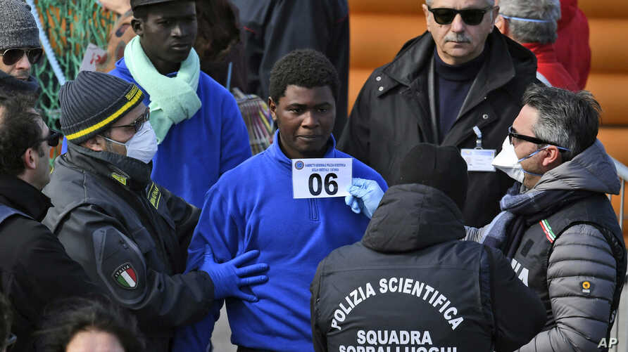 Migrants are photographed for identification as they disembark from the rescue ship Sea-Watch 3, which was carrying 47 migrants, as it docked at the Sicilian port of Catania, southern Italy, Jan. 31, 2019.